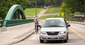 A car and bicyclist visiting campus